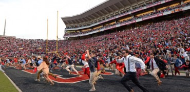 Fans rush the field after the game Saturday.